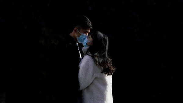 A couple wearing masks kiss at a main shopping area, in downtown Shanghai, China, as the country is hit by an outbreak of a new coronavirus, February 16, 2020 - Sputnik International