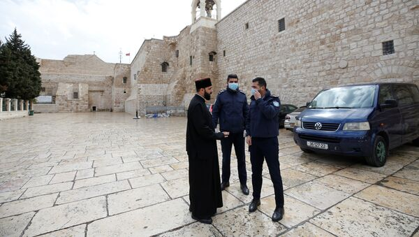 Palestinian police officers stand guard outside the Church of the Nativity that was closed as a preventive measure against the coronavirus, in Bethlehem in theWest Bank March 6, 2020 - Sputnik International