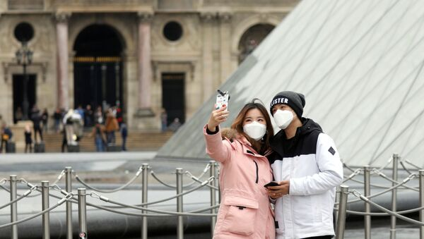 A couple wearing masks poses for a selfie near the Louvre Pyramid in Paris - Sputnik International