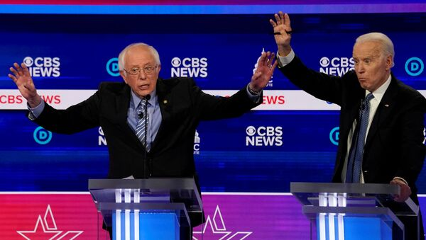 Democratic 2020 U.S. presidential candidates Senator Bernie Sanders and former Vice President Joe Biden brush hands as they have an exchange in the tenth Democratic 2020 presidential debate at the Gaillard Center in Charleston, South Carolina, U.S. February 25, 2020.  - Sputnik International