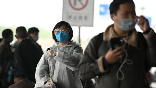 Passengers wearing protective facemasks arrive at the Changsha railway station in Changsha, the capital of Hunan province on March 8, 2020.   - Sputnik International