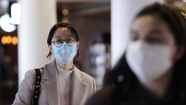 Travelers at Seattle-Tacoma International Airport wear masks Tuesday, March 3, 2020, in SeaTac, Wash. Six of the 18 Western Washington residents with the coronavirus have died as health officials rush to test more suspected cases and communities brace for spread of the disease. - Sputnik International