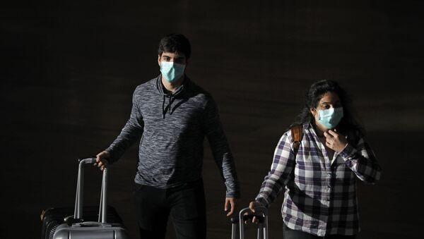 Passengers wear masks to help protect against coronavirus, at the Ben Gurion Airport near Tel Aviv, Israel, Sunday, March 8, 2020. - Sputnik International