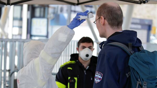A person wearing a protective suit and mask checks the temperature of people departing from the ferry port of Molo Beverello after Italy orders a countrywide lockdown to try and contain a coronavirus outbreak, in Naples, Italy, March 10, 2020.  - Sputnik International