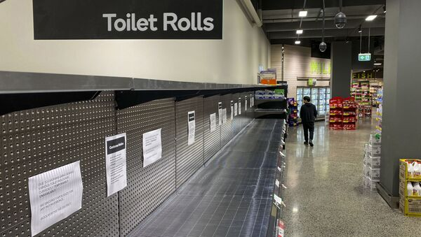 A shopper passes empty shelves usually stocked with toilet paper in a supermarket in Melbourne on March 5, 2020 - Sputnik International