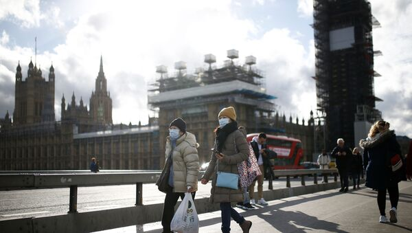 The Houses of Parliament can be seen as people wearing protective face masks walk across Westminster Bridge - Sputnik International