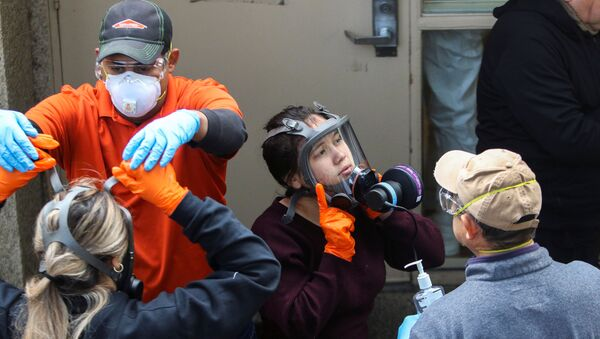 Members of a Servpro cleaning crew take off their protective gears as they exit the Life Care Center of Kirkland, the Seattle-area nursing home at the epicenter of one of the biggest coronavirus outbreaks in the United States, in Kirkland, Washington, U.S. March 11, 2020. - Sputnik International