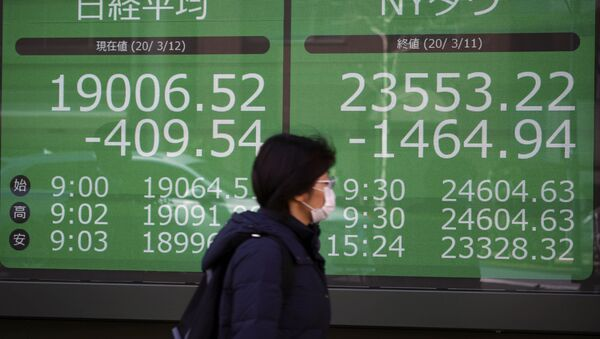 A woman walks past an electronic stock board showing Japan's Nikkei 225 and New York Dow index at a securities firm in Tokyo Thursday, March 12, 2020 - Sputnik International