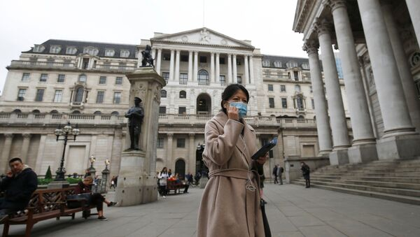 A woman, wearing a protective face mask, walks in front of the Bank of England, following an outbreak of the coronavirus, in London, Britain March 11, 2020 - Sputnik International
