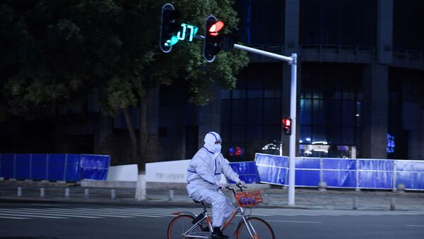 A man in a protective suit rides a shared bicycle at an intersection in Wuhan - Sputnik International