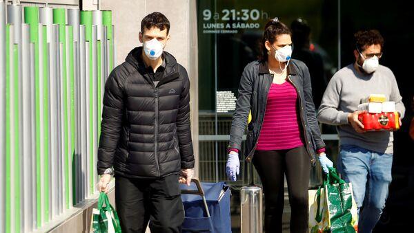 People wearing protective masks walk out of a supermarket, amidst concerns over Spain's coronavirus outbreak in central Madrid - Sputnik International