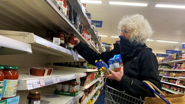 A shopper covers her face at a supermarket, as the number of coronavirus cases grow around the world, in London, Britain March 15, 2020.   - Sputnik International
