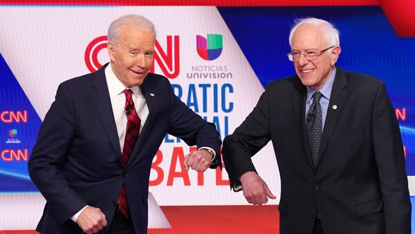 Democratic U.S. presidential candidates former Vice President Joe Biden and Senator Bernie Sanders do an elbow bump in place of a handshake as they greet other before the start of the 11th Democratic candidates debate of the 2020 U.S. presidential campaign, held in CNN's Washington studios without an audience because of the global coronavirus pandemic, in Washington, U.S. March 15, 2020. - Sputnik International