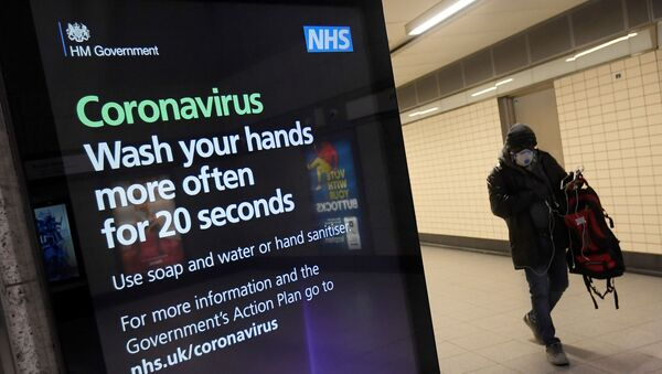 A man in a protective face mask walks past a British government public health campaign advertisement at Victoria underground station - Sputnik International