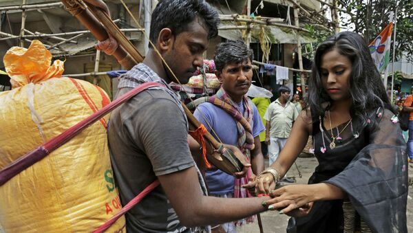 An Indian sex worker, right, ties a rakhi or a sacred thread on the wrist of a commuter as a symbolic gesture during Raksha Bandhan festival inside Sonagachhi, the biggest red light district in Kolkata, India, Monday, Aug. 7, 2017 - Sputnik International