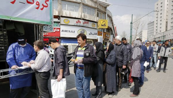 People queue in line to receive packages for precautions against COVID-19 coronavirus disease provided by the Basij, a militia loyal to Iran's Islamic republic establishment, from a booth outside Meydane Valiasr metro station in the capital Tehran on March 15, 2020. - Iran on March 15 announced that the new coronavirus has killed 113 more people, the highest single-day death toll yet in one of the world's worst-affected countries. - Sputnik International