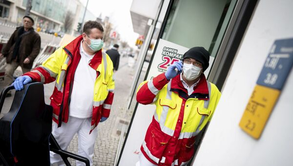 Paramedics from a patient transport company wearing face masks and gloves as they stand at the entrance to an apartment building to pick up a patient in the district Steglitz in Berlin, Germany, March 17, 2020 - Sputnik International