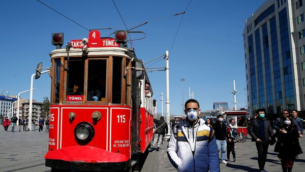 People wearing protective face masks, due to coronavirus disease (COVID-19) concerns, walk at Taksim square in central Istanbul, Turkey, March 17, 2020 - Sputnik International