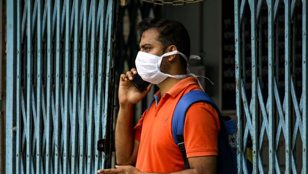 An Indian man wearing a mask talks on his mobile phone at a government run hospital where a special ward has been set aside for possible COVID-19 patients in Kolkata, India, Friday, March 6, 2020 - Sputnik International