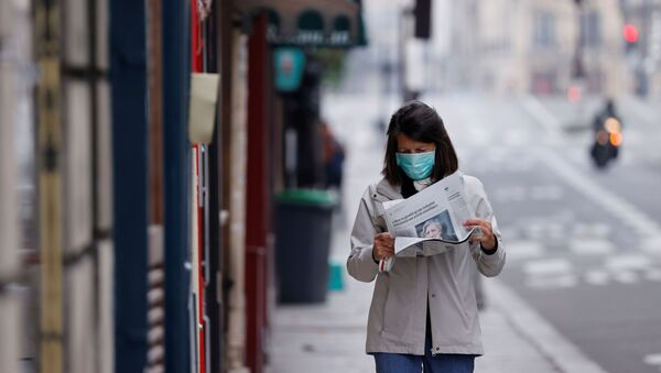 A woman wearing a protective face mask reads a newspaper as she walks in a street on the deserted Ile Saint Louis in Paris as lockdown is imposed to slow the rate of the coronavirus disease (COVID-19) in France, March 18, 2020. - Sputnik International