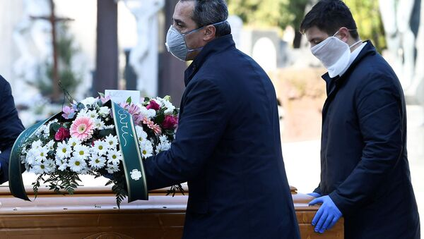 Cemetery workers and funeral agency workers in protective masks transport a coffin of a person who died from coronavirus disease (COVID-19), into a cemetery in Bergamo, Italy March 16, 2020 - Sputnik International