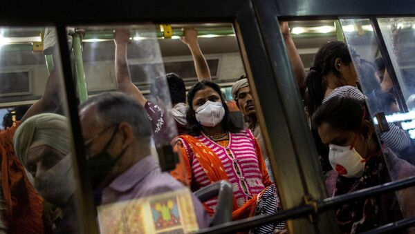 Commuters wearing protective masks as a precaution against the spread of coronavirus disease (COVID-19), travel in a crowded bus during evening rush hour, in New Delhi, India, March 18, 2020.  - Sputnik International