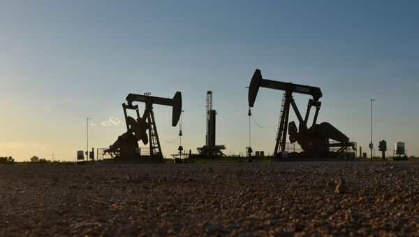 Pump jacks operate in front of a drilling rig in an oil field in Midland, Texas U.S. August 22, 2018. Picture taken August 22, 2018. - Sputnik International