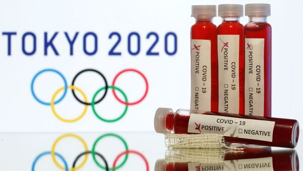 Fake blood in seen in test tubes labelled with coronavirus disease (COVID-19) in front of a displayed Tokyo 2020 Olympics logo in this illustration taken March 19, 2020 - Sputnik International