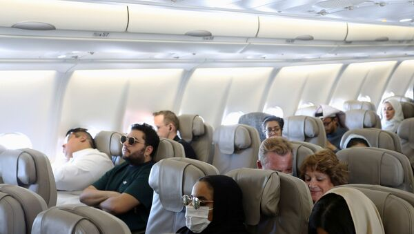 Passengers wear protective face masks following an outbreak of coronavirus, on a plane of Saudi Airlines, during their trip to al-Ula to attend the Tantura Festival, Saudi Arabia March 6, 2020 - Sputnik International