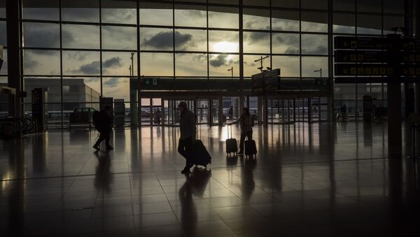 Passengers walk in an empty terminal at the airport of Barcelona, Spain, Thursday, March 19, 2020 - Sputnik International