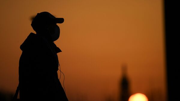 A person wearing a face mask is seen at the sunset as the spread of coronavirus disease (COVID-19) continues, in Milan, Italy March 21, 2020 - Sputnik International