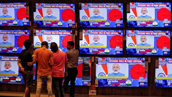 People watch Indian Prime Minister Narendra Modi addressing the nation amid concerns about the spread of coronavirus disease (COVID-19), on TV screens inside a showroom in Ahmedabad, India, March 19, 2020.  - Sputnik International