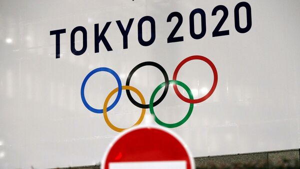 A banner for the upcoming Tokyo 2020 Olympics is seen behind a traffic sign, following an outbreak of the coronavirus disease (COVID-19), in Tokyo, Japan, March 23, 2020.  - Sputnik International