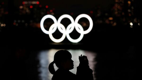 A woman takes a photograph in front of the giant Olympic rings at the waterfront area at Odaiba Marine Park in Tokyo, Japan, March 22, 2020. - Sputnik International