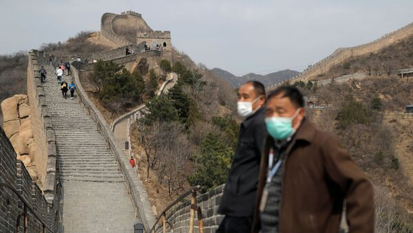 Men wearing protective masks stand as people hike along a section of the Great Wall in Badaling in Beijing, on its first day of re-opening after the scenic site's coronavirus related closure, China, 24 March 2020.  - Sputnik International