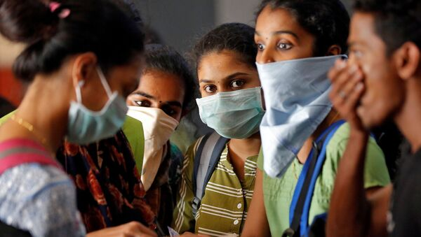 A group of students wearing protective masks wait to buy tickets at a railway station amid coronavirus fears, in Kochi, India, March 10, 2020 - Sputnik International