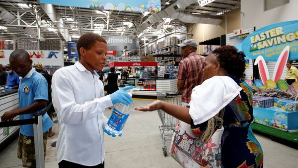 A store assistant gives people hand sanitiser as shoppers stock up on groceries at a Makro Store ahead of a nationwide 21 day lockdown in an attempt to contain the coronavirus disease (COVID-19) outbreak in Durban, South Africa, March 24, 2020. - Sputnik International