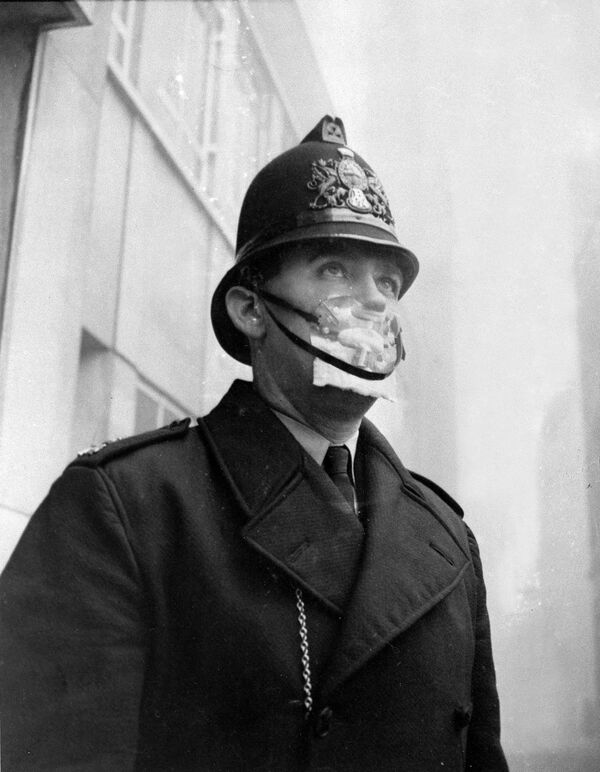 A British bobby, policeman, covers his mouth and nose with a mask to protect himself from the sulphurous smog in England on Dec. 5, 1962.  - Sputnik International