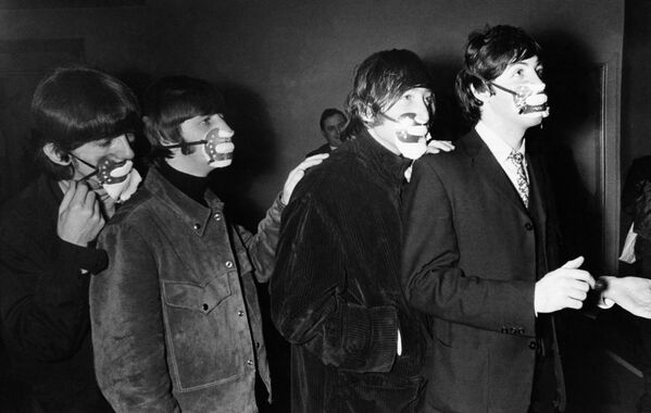 The Beatles are wearing the masks against the effects of fog. The famous beat group from Liverpool--George Harrison, Ringo Starr, John Lennon, and Paul McCartney , from left to right as they arrived for a concert in Ardwick, Manchester,  December 7, 1965  wearing masks.  - Sputnik International