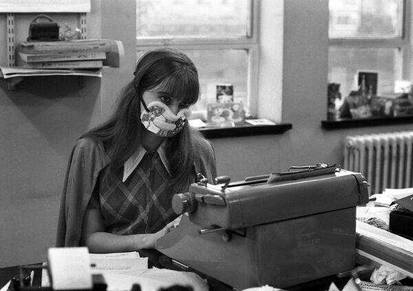 An office worker wearing an anti-flu mask sits at her type-writer in London, on January 1, 1970.  - Sputnik International