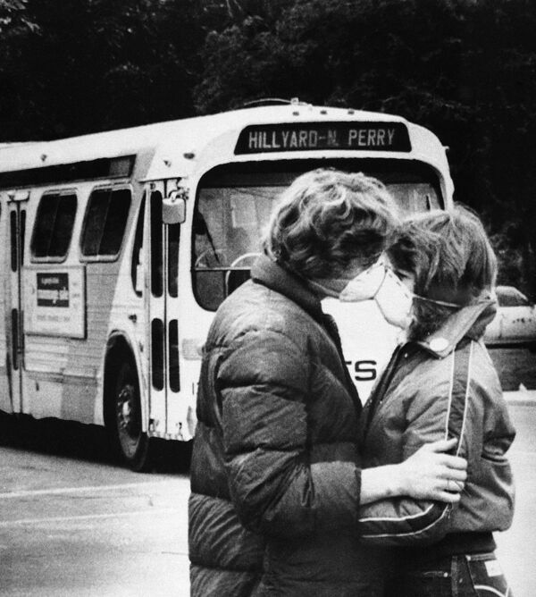 Fifteen-year-old Heidi Havens gives Allen Troup, 16, a kiss as he prepares to board a Spokane City bus, May 27, 1980. Spokane residents have had to wear face masks while outside for days now because of possible health threats from volcanic ash sprayed over the area by Mount St. Helens - Sputnik International