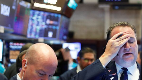 A trader reacts as he works on the floor of the New York Stock Exchange as markets continue to react to the coronavirus disease (COVID-19) at the NYSE in New York, U.S., 18 March 2020.   - Sputnik International
