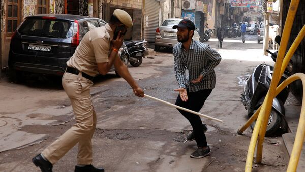 A police officer wields his baton against a man as a punishment for breaking the lockdown rules after India ordered a 21-day nationwide lockdown to limit the spreading of coronavirus disease (COVID-19), in New Delhi, India, March 25, 2020 - Sputnik International