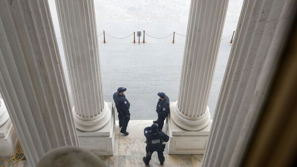 U.S. Capitol Police officers stand atop of the U.S. Senate stairway, ahead of a vote on the coronavirus relief bill, on Capitol Hill in Washington, U.S., March 25, 2020.  - Sputnik International