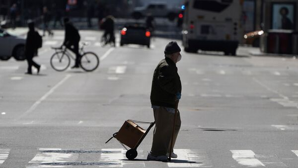 A pedestrian crosses a deserted 7th Ave in Times Square during the outbreak of Coronavirus disease (COVID-19), in the Manhattan borough of New York City, New York, U.S., March 26, 2020.  - Sputnik International