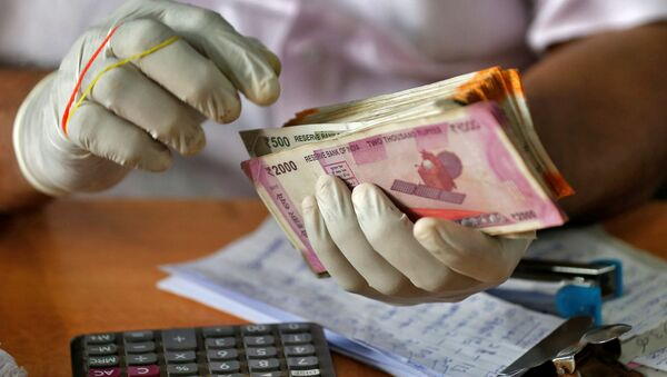 A trader wearing protective hand gloves counts Indian currency notes at a market during a 21-day nationwide lockdown to limit the spreading of coronavirus disease (COVID-19), in Kochi, India, March 27, 2020.  - Sputnik International