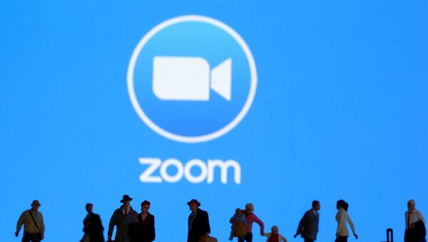 Small toy figures are seen in front of displayed Zoom logo in this illustration taken March 19, 2020.  - Sputnik International