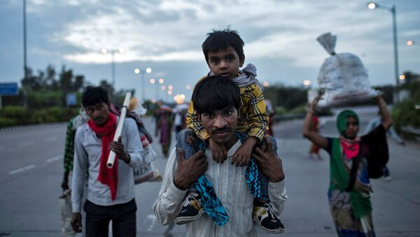A migrant worker carries his son as they walk along a road with others to return to their village, during a 21-day nationwide lockdown to limit the spreading of coronavirus - Sputnik International