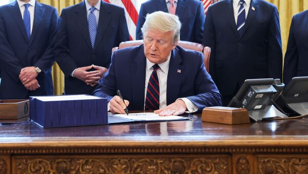 U.S. President Donald Trump signs the $2.2 trillion coronavirus aid package bill as he sits at the Resolute Desk in the Oval Office of the White House in Washington, U.S., March 27, 2020. - Sputnik International