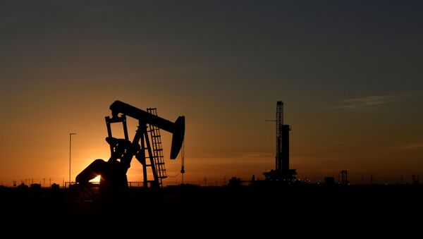 FILE PHOTO: A pump jack operates in front of a drilling rig at sunset in an oil field in Midland, Texas U.S. August 22, 2018. Picture taken August 22, 2018. - Sputnik International